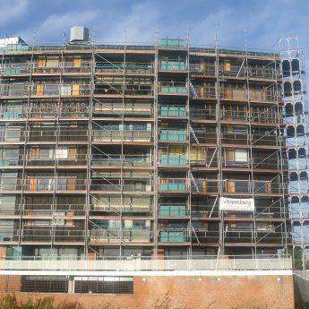Appartementencomplex rondom in de steigers waar de glasplaten werden vervangen voor nieuwe van veraf